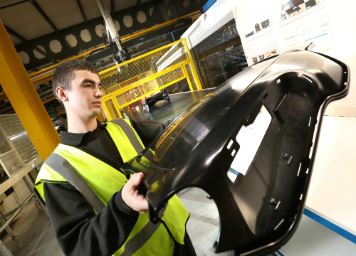 Jamie Wheeler, Production Operative at Omega Plastics with a component produced using the 1,300-tonne machinery.